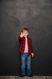 Photo of happy little boy standing over chalkboard and making thumbs up gesture. Looking at camera.