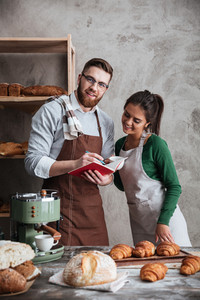 Photo of happy loving couple bakers standing near bread and croissants. Looking at notebook.