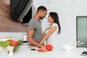 Photo of happy loving couple in the kitchen hugging while cooking.