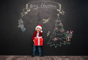 Photo of happy screaming child wearing hat standing near Christmas drawing on blackboard and holding a gift in hands. Looking at camera.