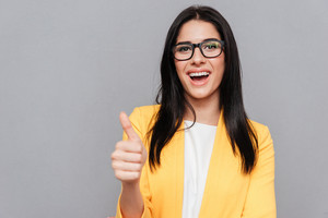 Photo of happy woman wearing eyeglasses and dressed in yellow jacket make thumbs up gesture over grey background. Look at camera.