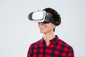 Photo of happy young asian man dressed in casual shirt in a cage and wearing virtual reality device. Isolated over white background.