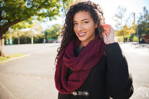 Photo of happy young dark skinned curly girl wearing scarf touching her hair against nature background. Look aside.