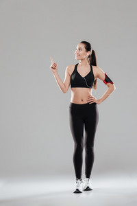Photo of happy young fitness lady standing over grey background listening music with earphones while pointing.