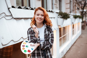Photo of happy young lady painter with red hair walking on the street. Look at camera while holding palette and paintbrush outdoors.