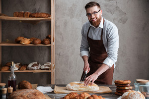 Photo of happy young man baker standing at bakery cut the bread. Looking at camera.