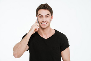 Photo of happy young man dressed in black t-shirt standing over white background talking by phone.