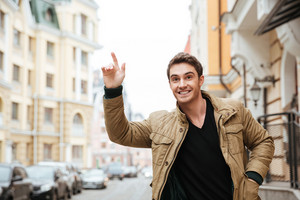 Photo of happy young man walking on the street and looking aside while catch the car.