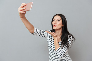 Photo of happy young woman send kissed while make a selfie over grey background. Look at phone.