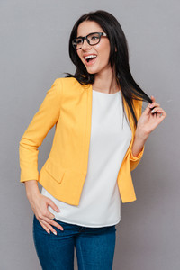 Photo of happy young woman wearing eyeglasses and dressed in yellow jacket posing over grey background. Look aside.