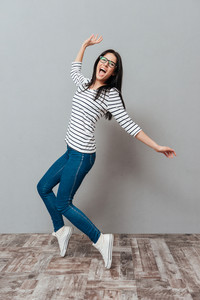 Photo of happy young woman wearing eyeglasses posing over grey background. Look at camera and screaming.