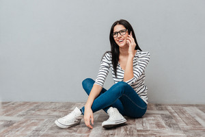 Photo of happy young woman wearing eyeglasses sitting on floor while talking by phone over grey background. Look aside.