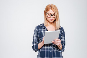 Photo of incredible woman wearing eyeglasses holding tablet computer isolated on a white background.