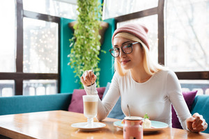 Photo of incredible young woman wearing hat and glasses eating cake and drinking coffee while sitting in cafe.