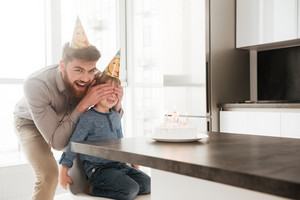 Photo of joyful bearded young father in the kitchen with his birthday little son covering his eyes.