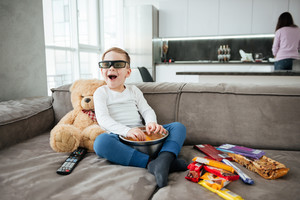 Photo of joyful boy on sofa with teddy bear at home watching TV with 3d glasses while eating chips. Holding remote control.
