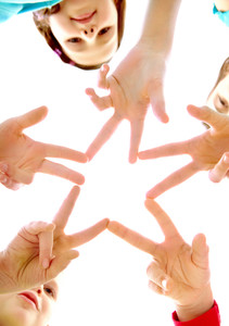 Photo of joyful children making star by their finger