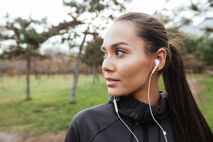 Photo of lady attractive runner in warm clothes and earphones in autumn park. Look aside.