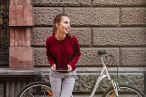 Photo of laughing young woman dressed in sweater standing near her bicycle on the street and using tablet. Look aside.