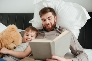 Photo of little boy lies at home in bed near toy with his bearded father reading fairytale book.