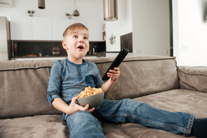 Photo of little boy sitting on sofa holding remote control while watching TV and holding popcorn in hands.