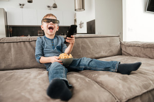 Photo of little boy sitting on sofa holding remote control while watching TV with 3d glasses holding popcorn in hands.