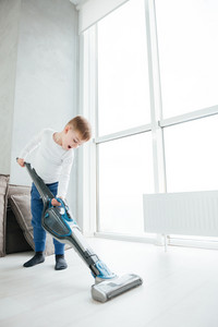 Photo of little cheerful boy cleaning the home. Look at floor.