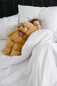 Photo of little cute boy sleeping with teddy bear in bed. Eyes closed.