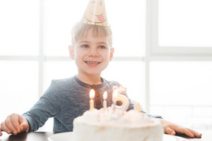 Photo of little cute happy birthday boy sitting in kitchen near cake while smiling. Look aside.