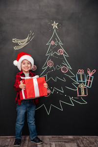Photo of little happy child wearing hat holding a big gift near Christmas tree drawing on blackboard. Looking at camera.