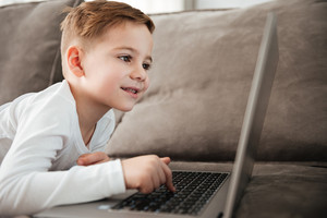 Photo of little joyful boy using laptop computer while lies on sofa at home. Look at laptop.