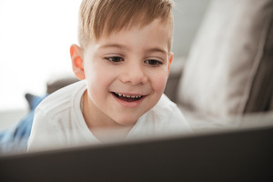 Photo of little smiling boy using laptop computer while lies on sofa at home. Look at laptop.