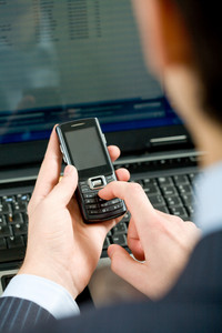 Photo of male hand holding cellular phone and writing sms