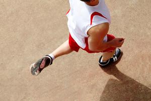 Photo of male in sportswear running down stadium track