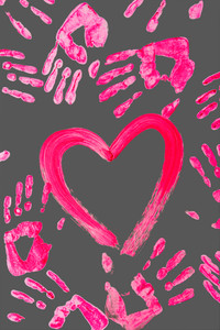 Photo of painted heart among imprints of human palms over grey background