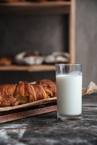 Photo of pastries on dark wooden table with milk at bakery