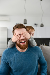 Photo of playful bearded father dressed in blue shirt playing with his little cute son who covering father's eyes indoors