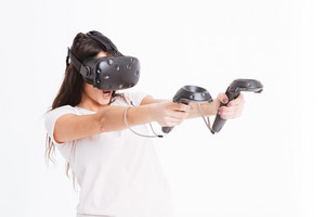 Photo of playful young lady wearing virtual reality device holding joysticks over white background.