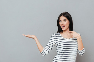 Photo of playful young woman standing over grey background while holding copyspace on hand and pointing on it. Look at camera.