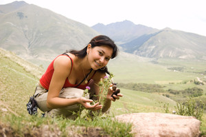 Photo of positive woman with cones in hands touching thorny plants on background of mountains in summer