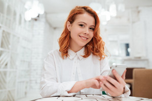 Photo of pretty redhead young woman dressed in white shirt chatting by her phone while sitting in cafe. Looking at camera.