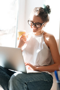 Photo of pretty young lady wearing glasses sitting near window at the home drinking juice and using laptop computer. Look at laptop.