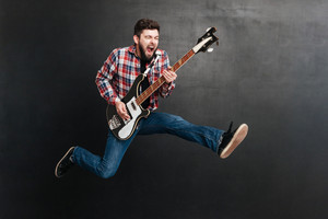 Photo of screaming man dressed in shirt in a cage jumping over chalkboard while playing on the guitar. Music concept.