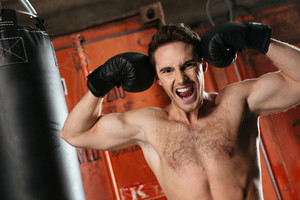 Photo of screaming strong boxer training in a gym with punchbag. Eyes closed.