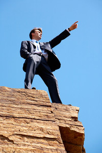 Photo of serious businessman standing on the cliff and pointing into the distance on the background of blue sky