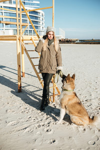 Photo of serious young woman walks in winter beach with dog on a leash.