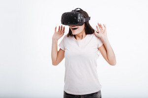 Photo of shocked happy lady wearing virtual reality device over white background.