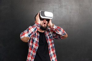 Photo of shocked man dressed in shirt in a cage and wearing virtual reality device standing over chalkboard