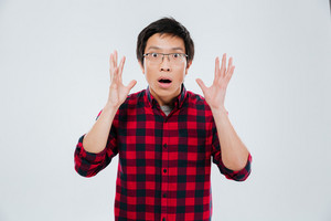 Photo of shocked young asian man dressed in casual shirt in a cage and wearing eyeglasses gesturing with hands. Isolated over white background. Look at camera.