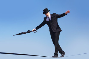 Photo of skilled businessman with folded umbrella walking down ribbon or rope